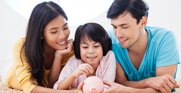 Image of a mom and dad and son putting money in a piggy bank
